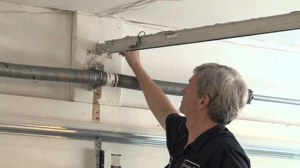 Garage door repair man performing garage door track repair.
